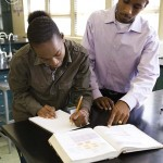 African teacher helping student in chemistry lab